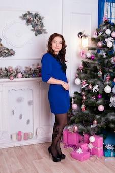 Mooi meisje in blauwe jurk in de buurt van de kerstboom.