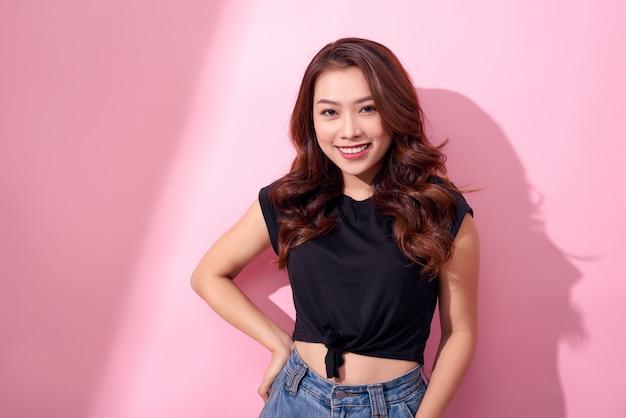 Mooi meisje in blauwe spijkerbroek en zwart shirt poseren, glimlachend op roze muur