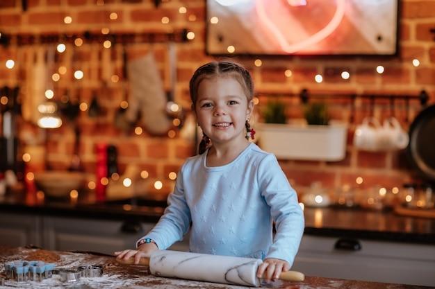 Mooi meisje in blauwe winter jurk en vlechten koken in de keuken met kerstmis.