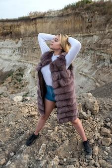 Mooi meisje in casual doek en bontjas zand rotsen