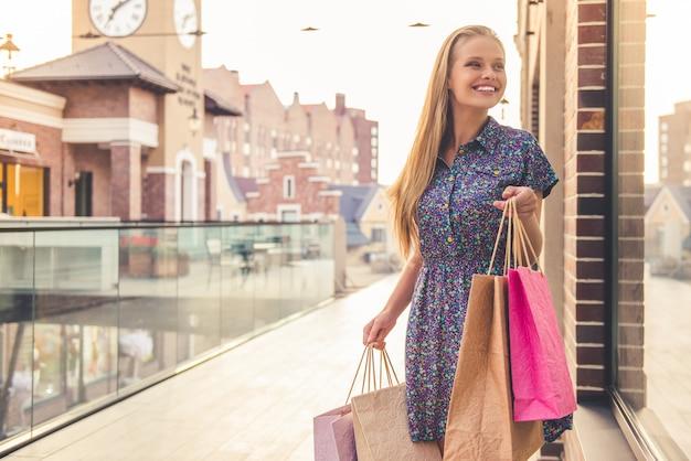 Mooi meisje in casual kleding houdt boodschappentassen.