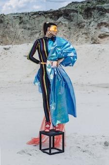 Mooi meisje in creatieve festivaloutfit, geel plastic masker en blauwe glanzende haarband