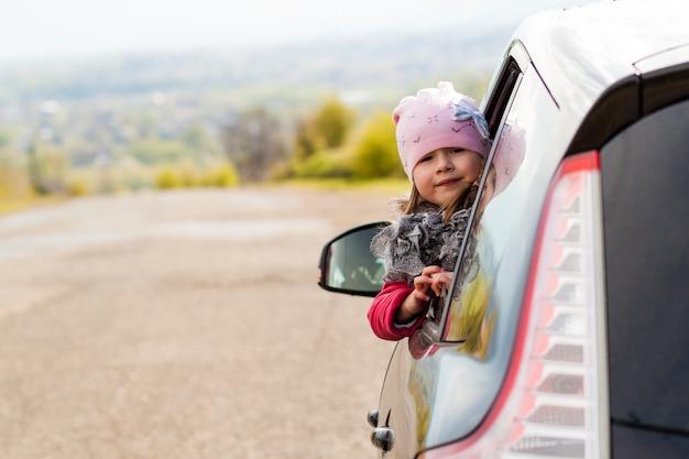 Mooi meisje in de auto die door autoraam kijkt.