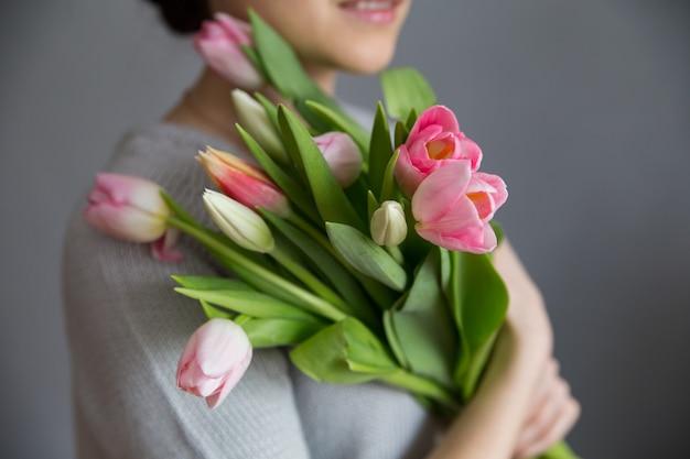 Mooi meisje in de blauwe jurk met bloementulpen in handen op een lichte achtergrond