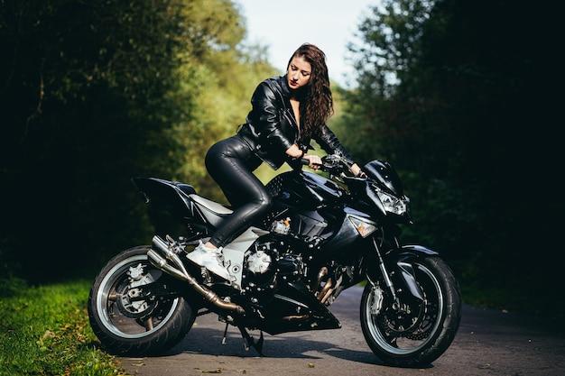 Mooi meisje in de buurt van de zwarte motorfiets, portret, in het bos in de buurt van de weg, herfst
