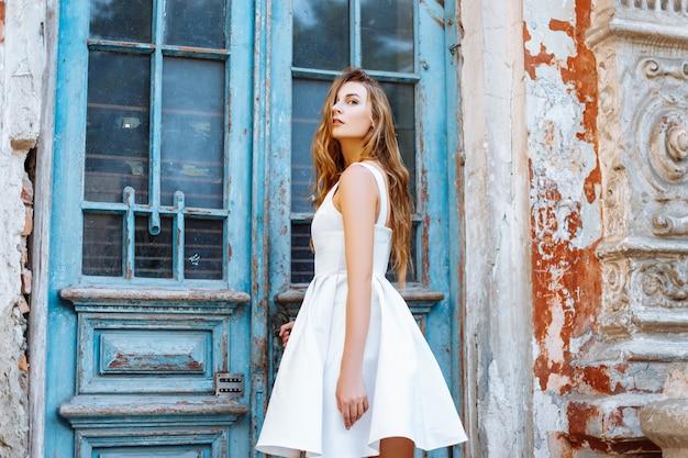 Mooi meisje in de buurt van een oude blauwe deur
