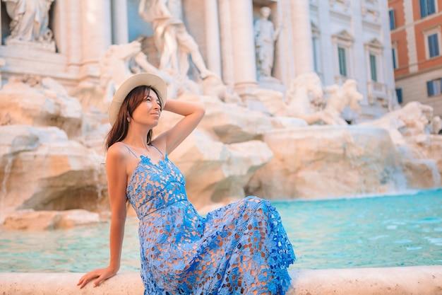 Mooi meisje in de buurt van fontein fontana di trevi met plattegrond van de stad