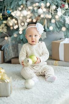 Mooi meisje in de buurt van versierde kerstboom