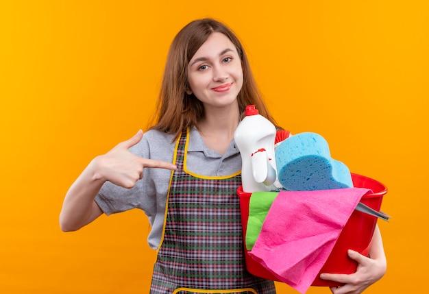 Mooi meisje in de emmer van de schortholding met het schoonmaken van hulpmiddelen die met wijsvinger naar het glimlachen zelfverzekerd richten