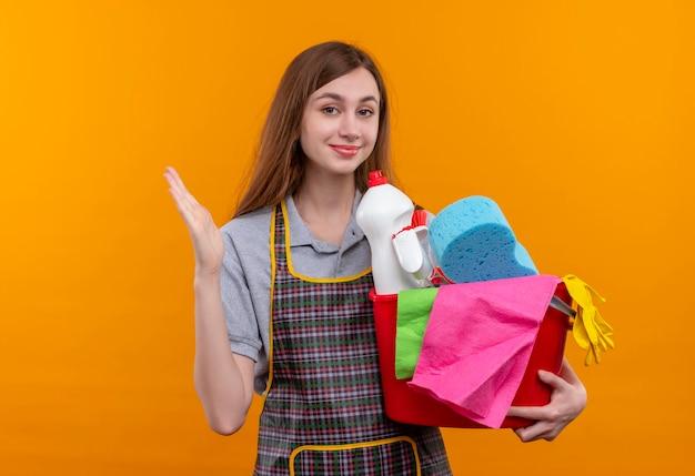 Mooi meisje in de emmer van de schortholding met het schoonmaken van hulpmiddelen die zelfverzekerd glimlachen, klaar om schoon te maken opheffen
