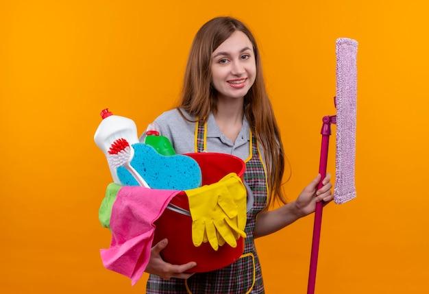 Mooi meisje in de emmer van de schortholding met het schoonmaken van hulpmiddelen en dweil vrolijk glimlachend