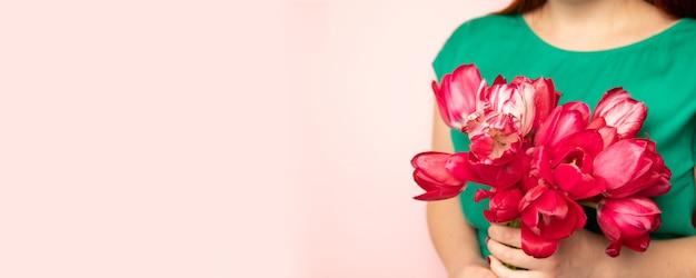 Mooi meisje in de groene jurk met bloemen tulpen in handen op roze