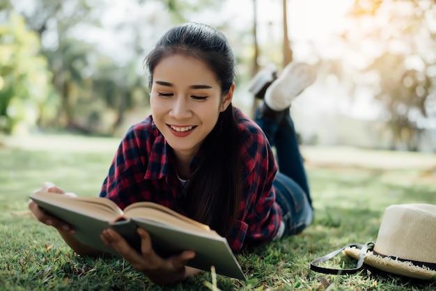 Mooi meisje in de herfstbos die een boek lezen