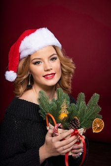 Mooi meisje in de hoed van de kerstman pronkt met haar wimpers en mooie make-up.