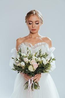 Mooi meisje in de kanten witte jurk met bloemen pioenrozen in handen op een lichte achtergrond