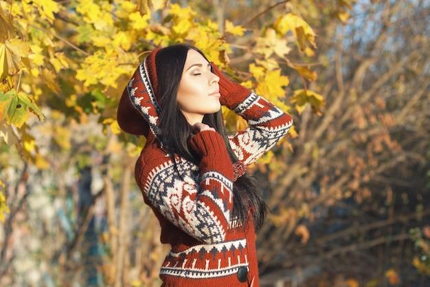 Mooi meisje in de kap in de herfst