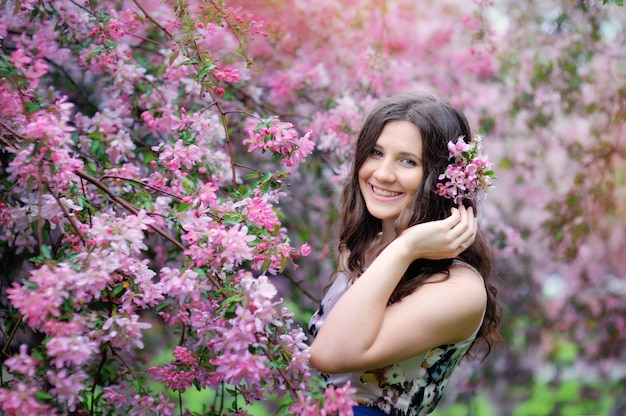 Mooi meisje in de lentepark met het portret van de bloemenlevensstijl