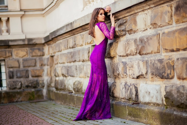 Mooi meisje in de paarse jurk leunde tegen de muur