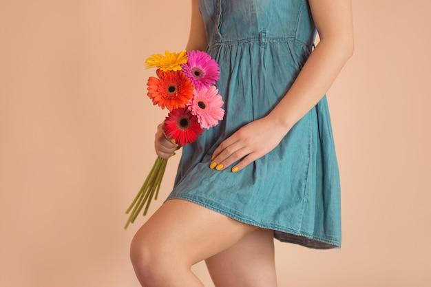 Mooi meisje in de spijkerjurk met kleurrijke verse bloemengerbera's. aantrekkelijk gelukkig meisje met een boeket bloemen in casual jeanskleding