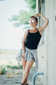 Mooi meisje in denim shorts en zwarte tanktop grunge-stijl