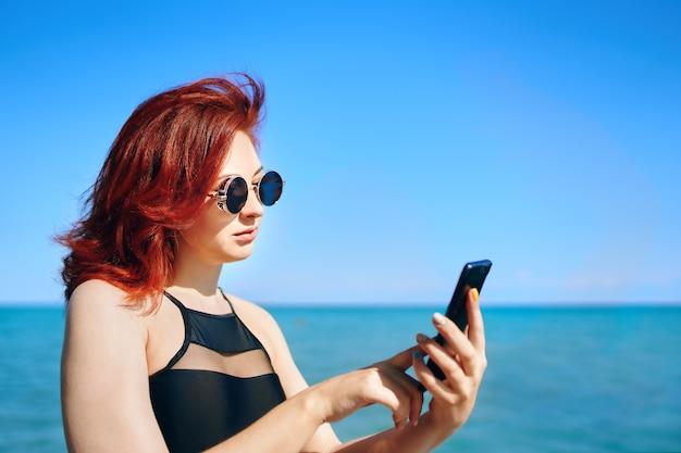 Mooi meisje in donkere zonnebril en zwarte zwembroek met smartphone in haar hand zonnige zomerdag redha...