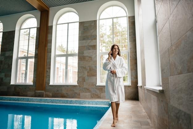 Mooi meisje in een badjas praten aan de telefoon bij het zwembad