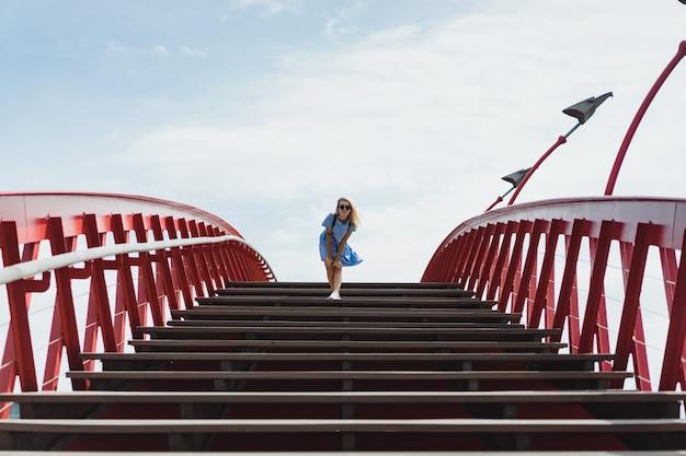 Mooi meisje in een blauwe jurk die zich voordeed op de brug