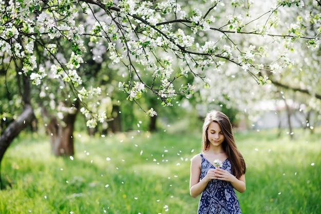 Mooi meisje in een blauwe jurk in een bloeiende appelboomgaard. allergie seizoen. sneeuw van bloemblaadjes.