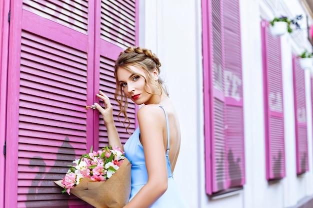 Mooi meisje in een blauwe jurk poseren op straat in de buurt van een café met roze ramen cafe