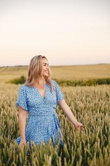 Mooi meisje in een blauwe jurk. vrouw in een zomer-veld.