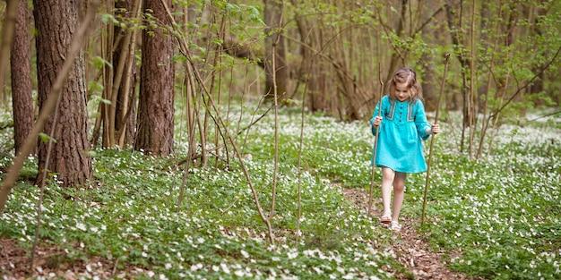 Mooi meisje in een blauwe jurk wandelen in het voorjaar hout. kind buiten spelen in de zomer. pasen. leuke tuinman die sneeuwdalingen plant. kopieer ruimte voor tekst. banner
