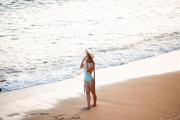 Mooi meisje in een blauwe zwembroek en hoed op een zandstrand aan zee in het zonlicht van de zonsondergang