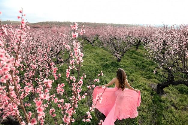 Mooi meisje in een bloeiende lentetuin. vrouw dresed in een trouwjurk