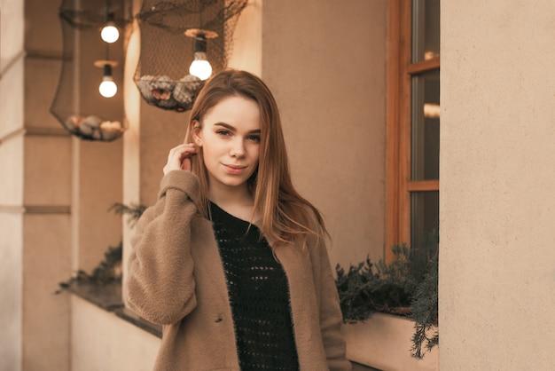 Mooi meisje in een bruine jas vormt op de camera in de buurt van de bruine muur, kijkt naar de camera en glimlacht