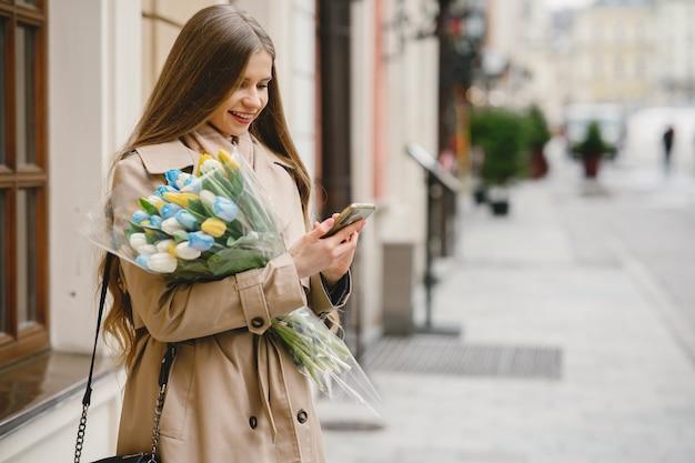 Mooi meisje in een bruine jas. vrouw in een lentestad. dame met boeket bloemen