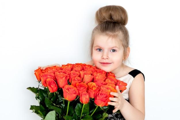 Mooi meisje in een elegante jurk met een boeket oranje rozen