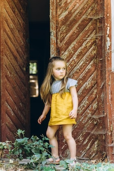 Mooi meisje in een gele jurk in de buurt van een houten deur