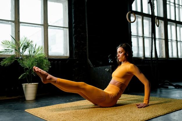 Mooi meisje in een gele sportkleding doet yoga correct ademen moderne sporthal