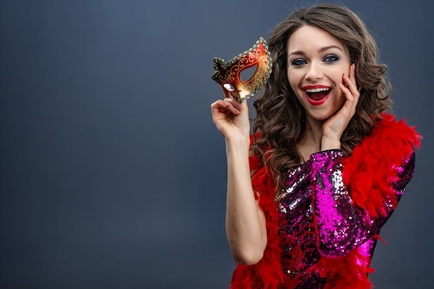 Mooi meisje in een glinsterende jurk en een boa om haar nek houdt een carnavalsmasker in verrukking