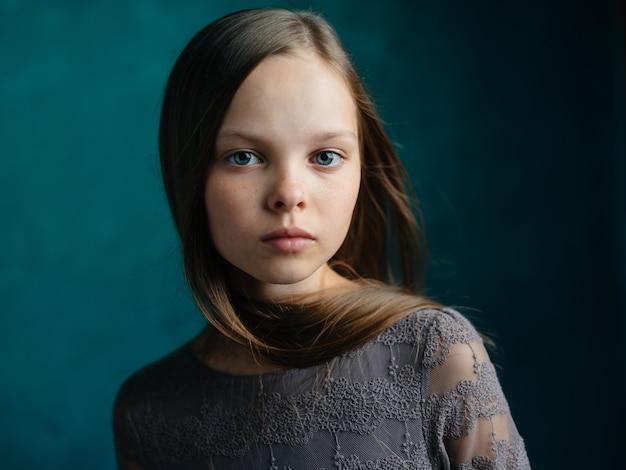 Mooi meisje in een grijze bijgesneden weergave van het kledings losse haar modelportret.