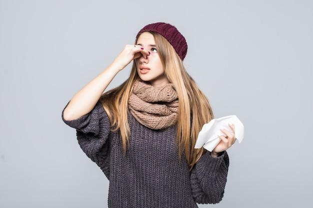 Mooi meisje in een grijze trui had koude griep hoofdpijn op grijs
