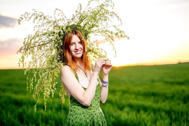 Mooi meisje in een groene jurk met een krans van bloemen