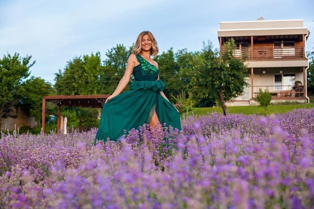 Mooi meisje in een groene jurk poseren op een lavendelveld