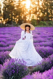 Mooi meisje in een grote hoed en een volle jurk op een achtergrond van lavendel. een jong model met vlechten in haar haar. zomerfoto in de zon.