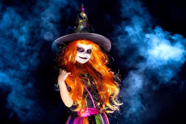Mooi meisje in een heks kostuum op een donkere achtergrond in rook