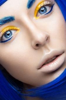 Mooi meisje in een helder blauwe pruik in de stijl van cosplay en creatieve make-up. Premium Foto