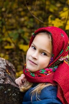 Mooi meisje in een heldere rode sjaal. portret van een meisje met bruine ogen in een oude russische sjaal op de achtergrond van de herfst. fotoshoot