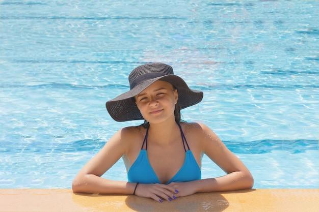 Mooi meisje in een hoed bij het zwembad