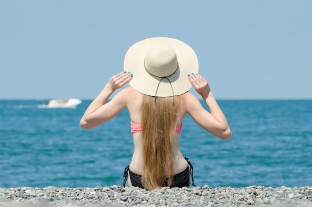 Mooi meisje in een hoed en zwembroek zit op het strand. zee en boot op de achtergrond. uitzicht vanaf de achterkant