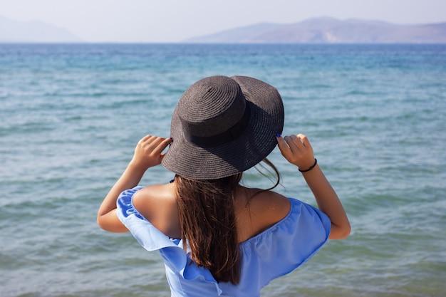 Mooi meisje in een hoed kijkt naar de zee